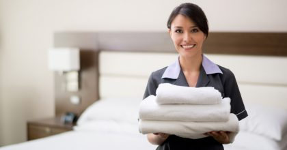 Maid working at a hotel holding towels and looking at the camera smiling - housekeeping concepts